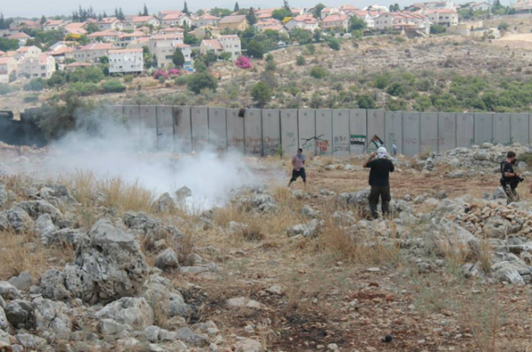 Protesters facing teargas in front of the annexation wall (Photo by ISM)