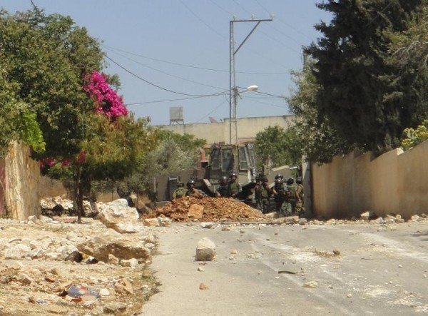 Soliders behind the new roadblock as the bulldozer retreates