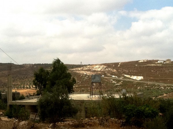 The illegal outpost of Havat Gilad on the right and the burnt land on the left (Photo by ISM)