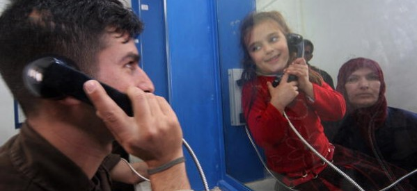 A prisoner talking to his daughter by phone and separated by a wall