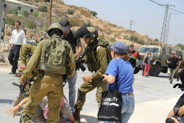 Soldiers violently pushing protester to the ground (South West Bank Popular Committee)