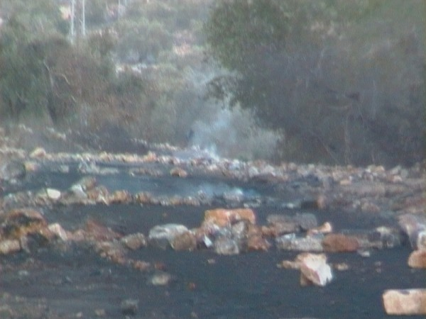 Road after Palestinian youths erected burning tires barricades (Photo by ISM)