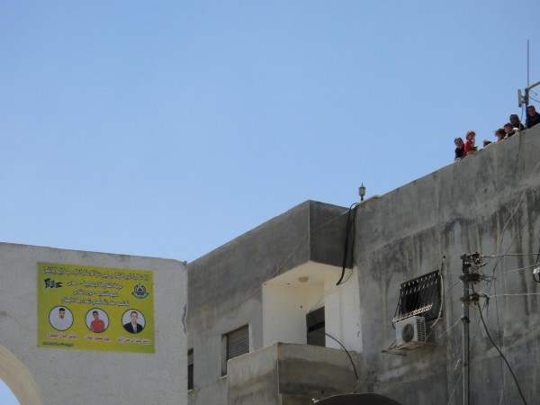 Poster showing the three martyrs, along with women on a roof overlooking the funeral march today.