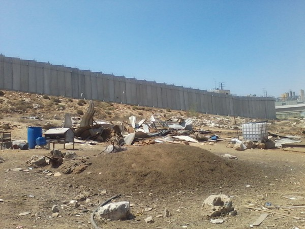 Destroyed homes and furniture in front of the Apartheid Wall (photo by ISM)
