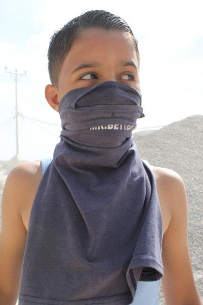 A boy wears his shirt as a mask to protect against tear gas. (Photo by Joe Catron)