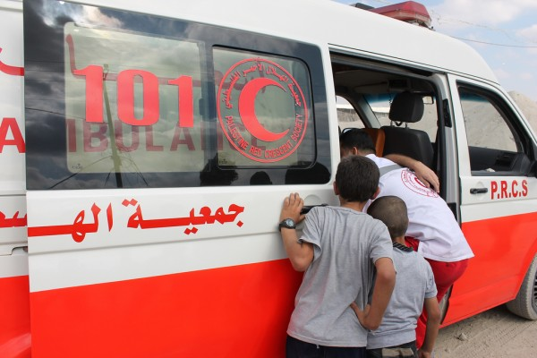 Boys watch as Palestinian Red Crescent Society medics help a demonstrator suffering from tear gas inhalation into an ambulance. (Photo by Joe Catron)