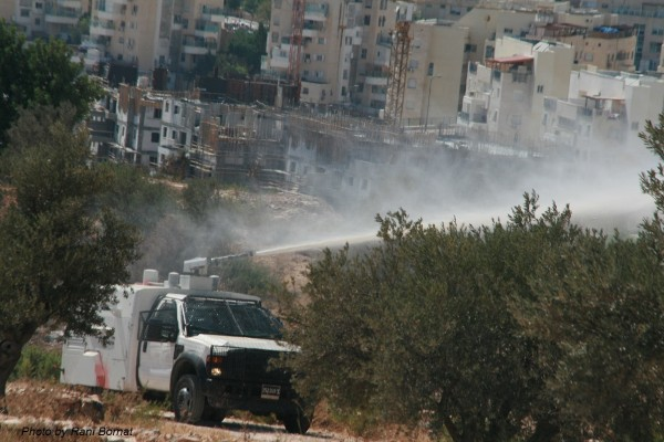 "Israeli occupation forces spraying protesters with ""skunk"" water (Photo by Rani Bomat)"