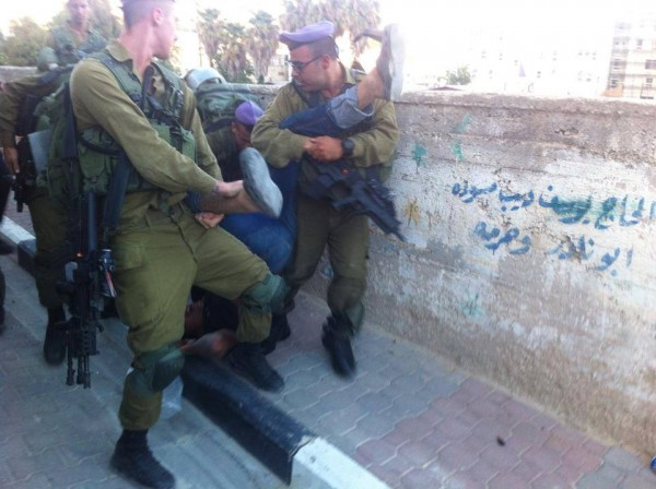 The Israeli army dropping Imad Al-Atrash on the ground (Photo by Youth Against Settlements)