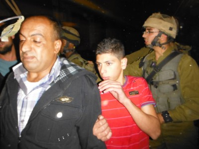The young teenager and his father with the Israeli soldiers
