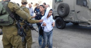 The children being detained by Israeli soldiers (photo by ISM).
