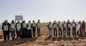 Palestinian and international activists hold signs in support of the Boycott, Divestment and Sanctions (BDS) movement by the buffer zone in Zeitoun on 9 February 2013.