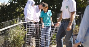 Palestinians view the fence around the Azzeh home