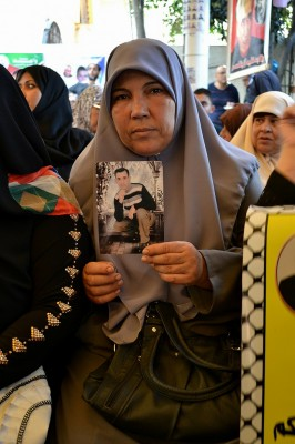 Rawda al-Najjar holds a picture of her detained son, Mohammed Ismail al-Najjar. (Photo by Rosa Schiano)