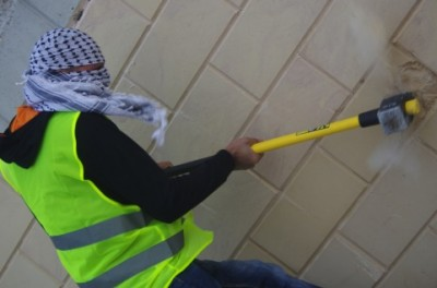 Palestinian activist smashes annexation wall with a sledgehammer (photo by Ingrid Bousquet).
