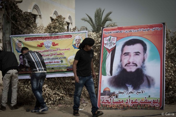 A young man walks past posters celebrating the release of Hilmi Hamad Obeid al-Amawi. (Photo by Gal·la López)