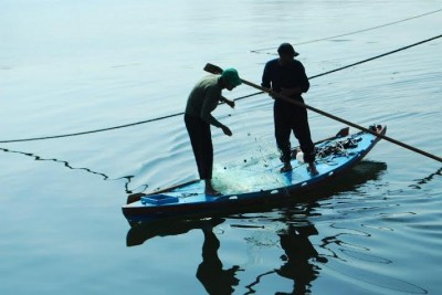 Two Palestinian fishermen paddle off the Gaza seaport. (Photo by Charlie Andreasson)