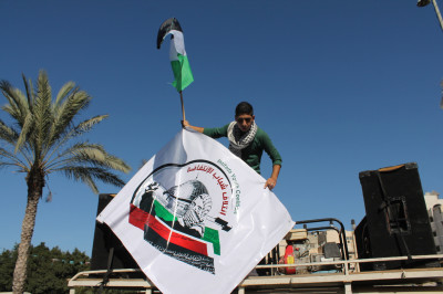An Intifada Youth Coalition activist waves the organization's banner from a sound truck. (Photo by Joe Catron)