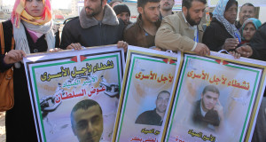 Fishermen and supporters hold posters with images of colleagues captured by Israeli forces, in Gaza City on 19 December 2013. (Photo by Joe Catron)