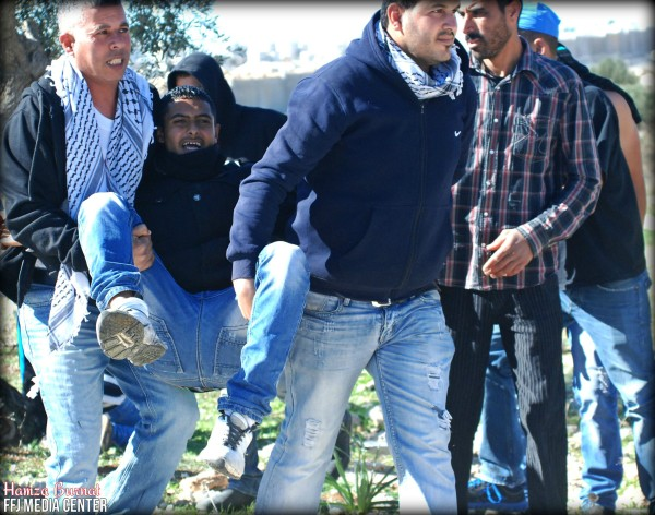 Demonstrators carry man shot in the foot by live ammunition (Photo by Mohammed Yasin/Hamza Burnat)