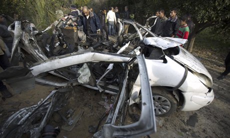 Palestinians gather next to a destroyed car after it was hit by an Israeli air strike in Beit Hanoun. Photograph: Mohammed Abed/AFP/Getty Images