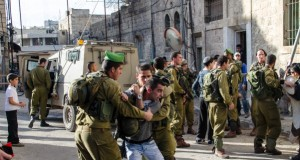 Israeli soldiers restrain one of the settlers responsible for the attack (Photo by ISM)