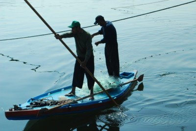 Two fishermen paddle a small boat off the Gaza coast. (Photo by Charlie Andreasson)