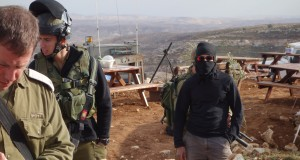Masked settlers and soldiers on Palestinian occupied hill (Photo by ISM)