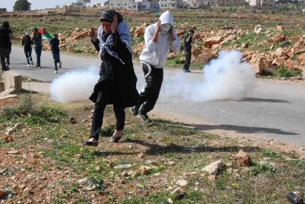 Palestinians taking cover from stun grenades fired by Israeli forces. 7th March 2014