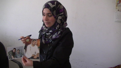 Mukarram Abu Alouf from the government Ministry of Detainees holds up two pictures of Rabee Ali, one before he was arrested and one on the day he was released. Rabee died soon after his release – photo taken by Corporate Watch, Gaza City, November 2013
