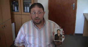 Akram Salameh holds up a picture of himself in prison uniform, taken inside Ramleh prison hospital – Photo taken by Corporate Watch, Gaza City, November 2013