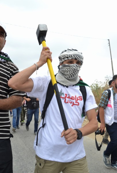 Activist carries a heavy craft hammer that was later used to damage the apartheid wall (photo by ISM).