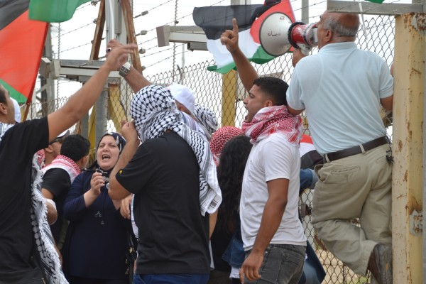 Palestinian women and men chanting at the gates of Natanya military checkpoint (photo by ISM).