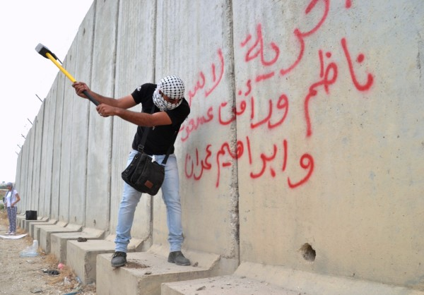 Two heavy craft hammers were used during the action to damage the apartheid wall near the checkpoint. Other protesters also had enough time to spray-paint messages onto the wall (photo by ISM).