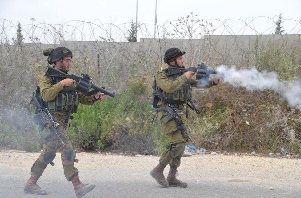 Israeli soldiers leave their positions at the checkpoint to fire teargas projectiles and canisters at the demonstrators. At least two people received a direct impact from teargas projectiles that were fired at the crowd (photo by ISM).