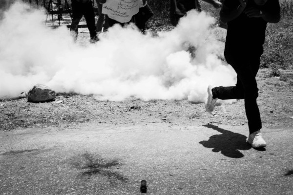 Even after the protesters were following the soldiers' instructions to stand behind the gate, the soldiers continued to throw tear gas and stun grenades at their feet (photo by ISM).