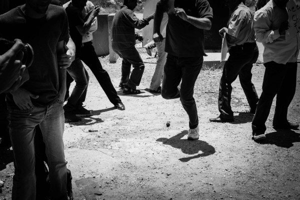 Protesters running away from a stun-grenade. Standing too close to a stun-grenade when it explodes, can result in hearing loss, concussion and loss of balance. (Photo by ISM)