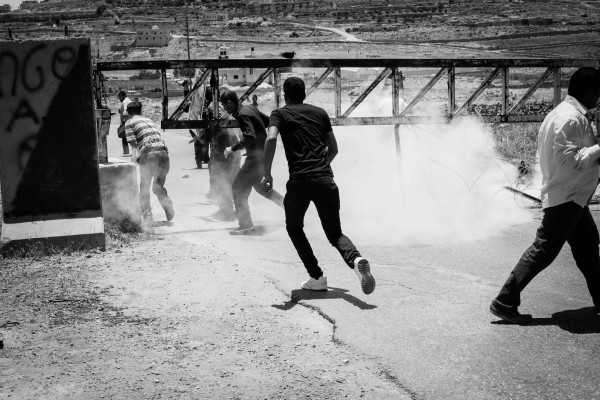 Protesters retreat after a tear gas grenade is thrown (photo by ISM).