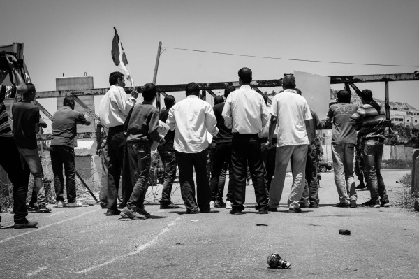 The demonstrators gathering behind the gate, continuing the protest (photo by ISM).