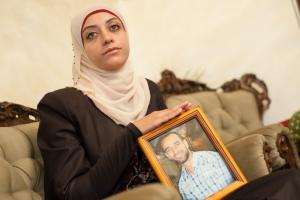 Shireen Essawi holding a photograph of her brother Samer