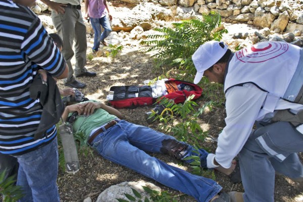 A Red Crescent paramedic attends to the injured youth (photo by ISM).