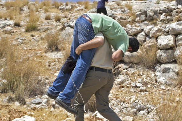 The injured 20-year-old is carried up a hill after injury from the Israeli military (photo by ISM).