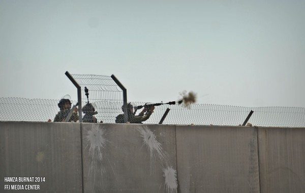 Soldiers fire tear gas canisters from behind the wall (photo by Sameer Bornat)
