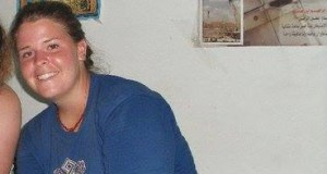 Kayla, sitting under a poster of Ashraf Abu Rahma from Bil'in