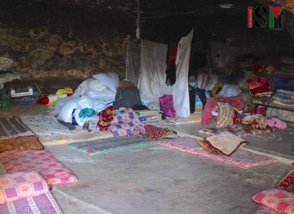 Inside one of the caves. Mattresses get spread around the floor in the evening to chat, share meals, watch tv and lay their heads.