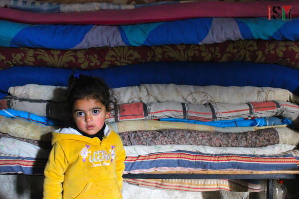 The second to youngest of Tuba, posing in front of the pile of mattresses.
