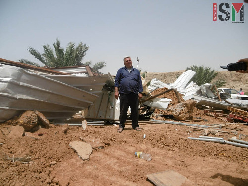 Fathe Abdullah Ahmad Tareeq in front of Mohammed Abu Amers family's demolished home.