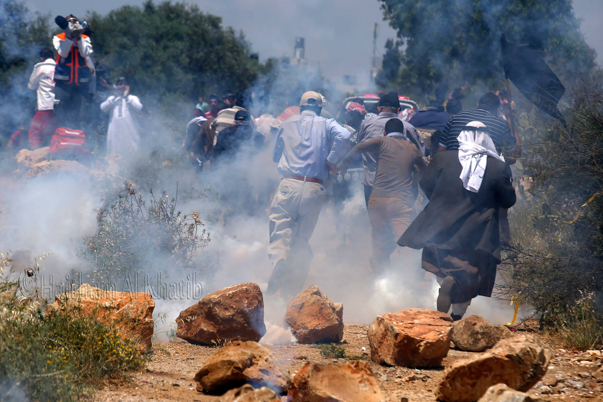 Protestors in Ni'lin running away from tear gas