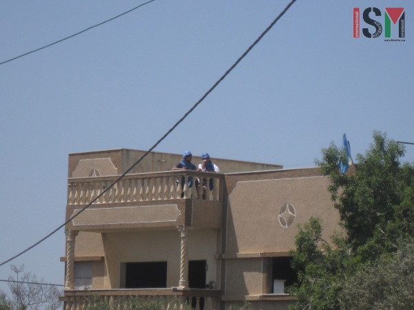 Two UN members observing the demonstration from a roof