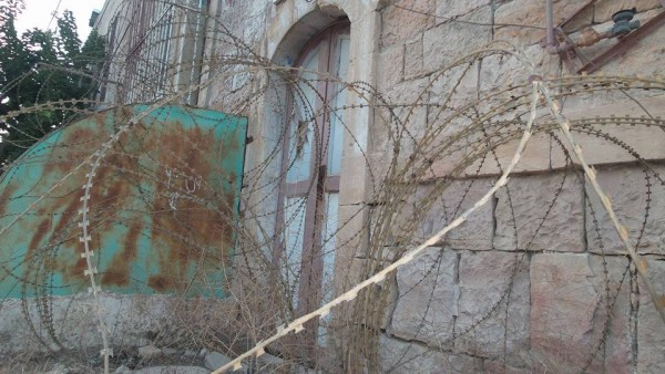 Barbed wire blocking the door to a house on Shuhada Street.