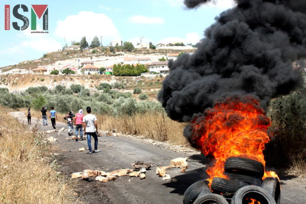 Rubber tires set alight on the road to the illegal settlement Qedumim
